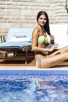 schöne junge Frau beim Sonnenbaden am Pool