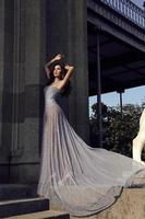 schöne Frau mit dunklem Haar trägt luxuriöses Kleid