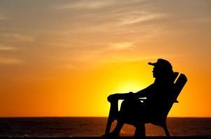 Frau, die tropischen Sonnenuntergang genießt foto