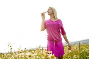 schöne Frau, die Gänseblümchen in einem Feld genießt