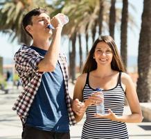 glückliches Paar, das Wasser aus Plastikflaschen genießt foto
