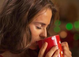 junge Frau, die Tasse heiße Schokolade genießt