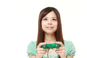 junge japanische Frau, die ein Videospiel genießt foto