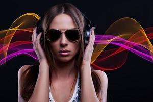 Frau DJ genießt die Musik in Kopfhörern foto