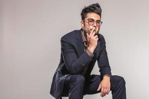 junger eleganter Mann, der seine Zigarre genießt, während er sitzt foto