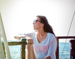 schönes Mädchen, das die Sonne auf einer Yacht genießt foto