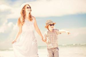glückliche schöne Mutter und Sohn genießen Strandzeit foto