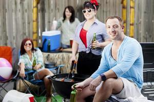 tailgating: glückliche Gruppe von Freunden, die Grill im Freien genießen