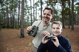 Vater und Sohn genießen die malerische Aussicht mit einem Fernglas foto