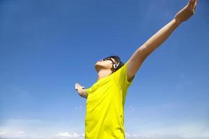 junger Mann, der Musik mit blauem Himmelhintergrund genießt foto
