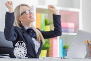 glückliche junge Frau genießt es, den Job pünktlich zu beenden foto