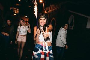 fröhliche junge Frau, die eine Wunderkerze hält, die in Partei genießt foto