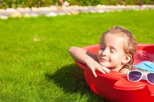 Porträt des entspannenden entzückenden kleinen Mädchens, das ihren Urlaub genießt