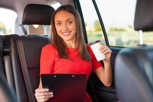fröhliche junge Frau genießt heißes Getränk im Auto
