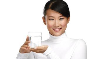 junge asiatische chinesische Frau, die ein Glas Wasser genießt foto