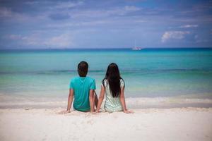 junges Paar, das sich am weißen Sandstrand genießt foto