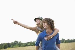 glückliche Frau, die etwas zeigt, während sie huckepack genießt