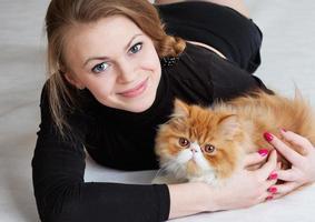 das nette Mädchen mit einer roten Katze an den Händen
