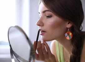 junge schöne Frau, die Make-up nahe Spiegel macht foto