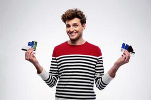 glücklicher lässiger Mann, der Kreditkarten hält