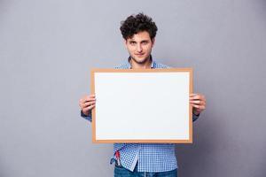 lässiger junger Mann, der leeres Brett hält foto