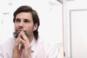 junger Mann, der im Büro sitzt und aufschaut foto