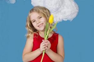 Mädchen in einem roten Kleid, das eine gelbe Tulpe hält foto