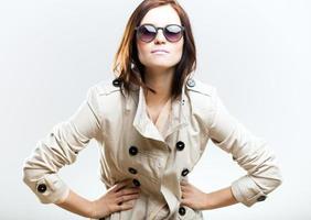 lächelnde modische Frau im Mantel mit Sonnenbrille