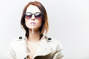 modische Frau in Mantel und Sonnenbrille mit Zigarette