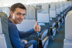 glücklicher Mann, der Daumen oben im Flugzeug zeigt foto