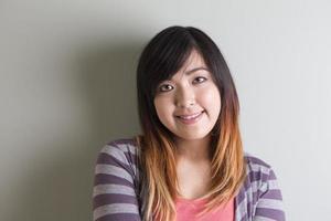 asiatische Frau, die auf grauem Hintergrund steht