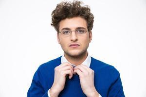Geschäftsmann in Brille glättet seine Krawatte foto