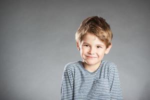 Porträt des Jungen, Emotion, Lächeln, grauer Hintergrund foto