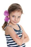 selbstbewusstes kleines Mädchen vor dem weißen Hintergrund foto