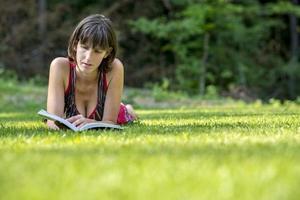 Frau, die auf dem Gras liegt, während sie ein Buch liest