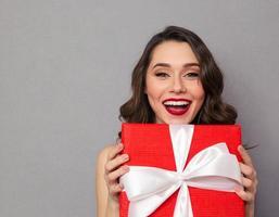 fröhliche Frau, die Geschenkbox hält foto