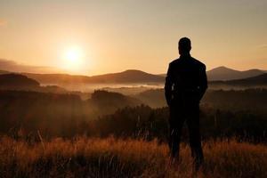 Wanderer auf Wiese mit goldenen Grashalmen, Sonnenaufgang foto