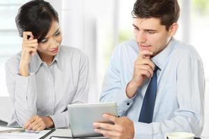 Geschäftspartner, die beim Meeting das Touchpad verwenden foto