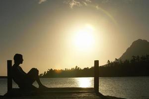 Mann sitzt auf Dock am See foto