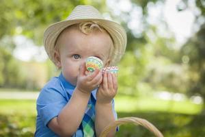 süßer kleiner Junge, der seine Ostereier draußen im Park genießt