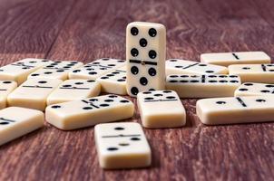 Dominostücke auf dem braunen hölzernen Tischhintergrund
