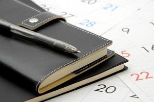 persönlicher Veranstalter und Stift auf Kalender foto
