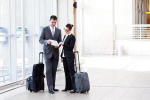 Mann und Frau in Geschäftskleidung mit Gepäck foto