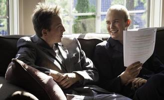 Zwei junge Erwachsene, die Spaß haben, erklären währenddessen eine Zeitung foto