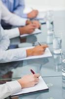 Nahaufnahme von Arbeitskollegen, die während der Präsentation Notizen machen