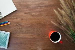 Arbeitsbereich mit Gras, Notizbuch, Kaffee, Stiften auf dem Tisch