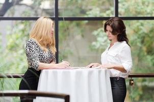 Zwei Geschäftsfrauen unterhalten sich in einem Café foto