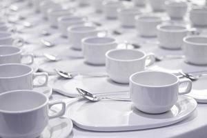 Stapel Kaffeetassen mit silbernen Teelöffeln bereiten sich auf das Treffen vor foto