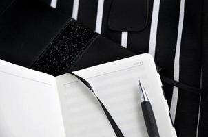 Stift auf Notizbuch mit schwarzem Hintergrund