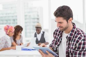 Gelegenheitsgeschäftsmann, der digitales Tablett verwendet foto